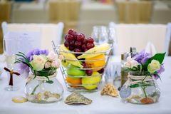 Wedding table arrangement with flower bouquets and fruit basket stock images