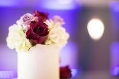 Wedding Table Arrangement - Multi Colored Roses in a White Vase. Table Arrangement - Multi Colored Roses in a White Vase with beautiful purple lights and bokeh Stock Images
