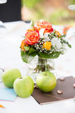 Wedding table centerpiece. Roses in arrangement in glass vase on white tablecloth with green apples for outdoor wedding banquet Royalty Free Stock Images