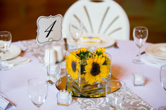 Wedding Table Centerpieces with Flowers. Flowers in glass on the tables for the centerpieces at this indoor wedding reception Stock Photo