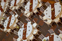 Wedding table and chairs. Classic wedding chairs and table setting shot from above. Multiple tables, table cloth and party favors Stock Photos