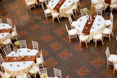 Wedding table and chairs. Classic wedding chairs and table setting shot from above. Multiple tables, table cloth and party favors Stock Photography