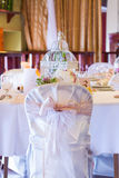 Wedding table and chairs with vintage decoration. White wedding chairs with lace ribbon Royalty Free Stock Image
