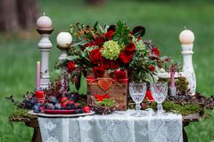 Wedding table decor: chairs and candles, flowers, ceramic dishes with fruits, standing on the lace tablecloth and moss. Bridal det. Ails and decorations Stock Images