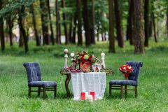 Wedding table decor: chairs and candles, flowers, ceramic dishes with fruits, standing on the lace tablecloth and moss. Bridal det. Ails and decorations Royalty Free Stock Photos