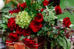 Wedding table decor: flowers composition with roses,berries, herbs and greenery standing in wooden box. Bridal details and decorat. Wedding table decor: flowers Royalty Free Stock Photo