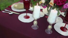 Wedding table decor at the nature with lighted candles. Steadicam shot stock video footage