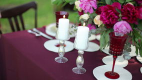 Wedding table decor at the nature with lighted candles. Steadicam shot stock footage