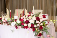 Wedding table decor with red flowers and candles.  royalty free stock photo