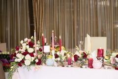 Wedding table decor with red flowers and candles.  stock image