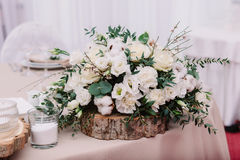 Wedding table decorated with bouquet and candles. Wedding table decorated with candles and bouquet, which consist of buttercup, lavender, cotton and roses Stock Image
