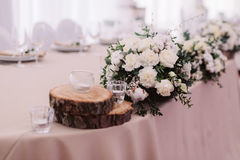 Wedding table decorated with bouquet and candles. Wedding table decorated with candles and bouquet, which consist of buttercup, lavender, cotton and roses Royalty Free Stock Photo