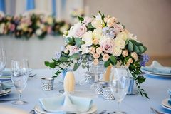 Wedding table decorated with a bouquet of flowers roses closeup. Wedding table decorated with a bouquet of flowers roses and delphinium. Tablecloth blue candles Stock Images