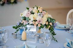 Wedding table decorated with a bouquet of flowers roses closeup. Wedding table decorated with a bouquet of flowers roses and delphinium. Tablecloth blue candles Stock Photo