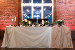 Wedding table decorated with flowers. Stylish wedding table decorated with flowers on wall of bricks background Royalty Free Stock Photos