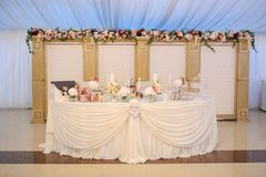 Wedding table decorated with flowers:. Hortensia, roses and eustoma. Design elements: box, candles and watering Royalty Free Stock Images