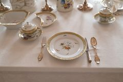 Wedding table decoration with expensive retro royal majesty porcelain service plates and cutlery in a palace stock image
