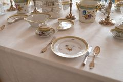 Wedding table decoration with expensive retro royal majesty porcelain service plates and cutlery in a palace royalty free stock image