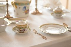 Wedding table decoration with expensive retro royal majesty porcelain service plates and cutlery in a palace royalty free stock photo