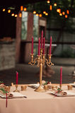 Wedding table decoration. Flowers composition withe candle in a candletick Royalty Free Stock Photography