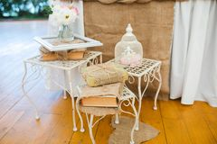 Beautiful wedding table decoration of forged vintage white pedestals, cages, books wrapped in a linen cloth, a wooden frame and fl. Wedding table decoration of Royalty Free Stock Photos