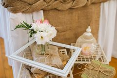 Beautiful wedding table decoration of forged vintage white pedestals, cages, books wrapped in a linen cloth, a wooden frame and fl. Wedding table decoration of Stock Photography