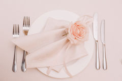 Wedding table decoration of the napkin with the light pink rose on the plate Royalty Free Stock Image