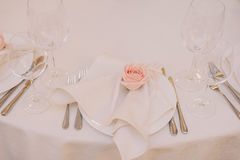 Wedding table decoration of the napkin with the light pink rose on the plate Royalty Free Stock Images