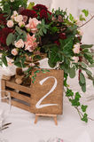 Wedding table decoration with the red and pink flowers and wooden box stock images
