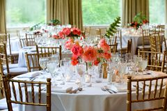Wedding table decoration series - tables set for beautiful indoor catered luxury wedding event with flower arrangements. Wedding tables set for fine dining stock image