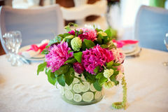 Wedding table decoration, transparent vase with sliced citrus, pink peonies against the white tablecloth. royalty free stock photos