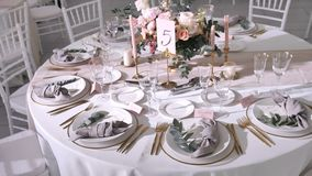 Wedding table decorations for guests in modern style, flower arrangement with roses and eucalyptus, pastel colors
