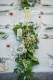 Wedding table with exclusive floral arrangement prepared for reception, wedding or event centerpiece in greenery style.  stock photos