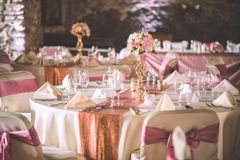 Wedding table with exclusive floral arrangement prepared for reception, wedding or event centerpiece in rose gold color.  stock photos