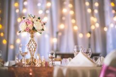 Wedding table with exclusive floral arrangement prepared for reception, wedding or event centerpiece in rose gold color.  royalty free stock photography