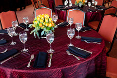Wedding Table with a red tablecloth. A table set for fine dining during a catered event Stock Photography