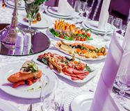 Wedding table served with tasty meals, antipasto platter cold meat, fish platter, cheese platter. Holiday banquet menu