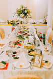 The wedding table set consisted of different dishes and the huge bouquet placed on the table. Royalty Free Stock Image