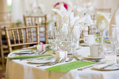 Wedding table set for fine dining. This is a wedding table set for dinner service. There are green menus on the table, but you cannot read the writing Stock Photo