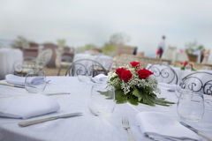 Wedding table set with white linen and red roses Stock Photos