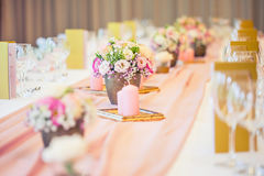 Wedding table setting. Beautiful table set with flowers and glass cups for some festive event, party or wedding reception.  stock image