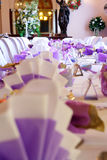 Wedding table setting, portrait. View along a table setting towards a large mirror. Table setting is predominantly white and violet with gold trimmings Stock Photos