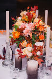 Wedding table setting in rustic style. close up. Luxury wedding decorations with bench, candle and flowers composition on ceremony place Royalty Free Stock Image