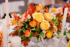 Wedding table setting in rustic style. Elegant festive table setting with colorful flowers, cutlery, candles. Wedding table decoration Stock Image