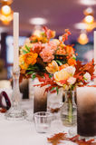 Wedding table setting in rustic style. Luxury wedding decorations with bench, candle and flowers composition on ceremony place Stock Photo