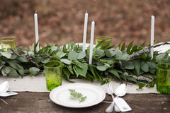 Wedding table setting with white plates. And green glasses decorated with white candles, green leaves and eucalyptus outdoors. Wedding decor concept. Decorated Royalty Free Stock Photography