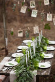 Wedding table setting. With white plates and green glasses decorated with white candles, green leaves and eucalyptus outdoors Royalty Free Stock Photo