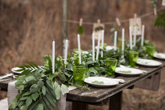 Wedding table setting. With white plates and green glasses decorated with white candles, green leaves and eucalyptus outdoors Royalty Free Stock Photography