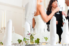 Wedding table at a wedding feast. Decorated with flowers – in the background the bride