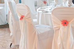 Wedding table with white linen and covered chairs. Portion of a wedding table with white linen, surrounded by chairs and white chair covers with an ornamental Stock Photo